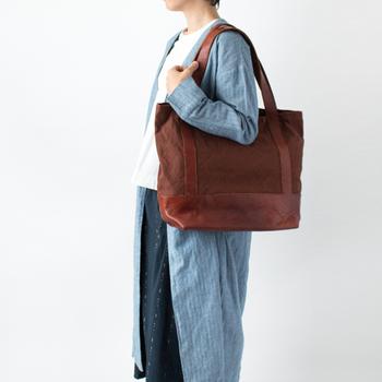 倉敷帆布で作られた、シックな茶色のトートバッグ。しわのある帆布と、ベジタブルタンニンで鞣されたヌメ革というこだわりの詰まったアイテムです。