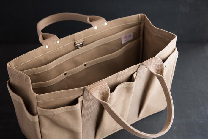 Mサイズはちょっとした毎日の荷物を持ち運ぶのに丁度いいサイズ。開口部にフックが付いていて、荷物の飛び出しなどを防いでくれる。ポケットが多く、アウトドアなどでも活躍してくれるはず。