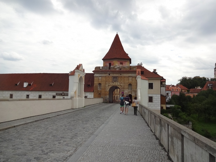 チェスキー・クルムロフの鉄道駅から約1.5キロメートル南に位置するブディヨヴィツェ門は、宝石箱のように美しい街並みをした旧市街への入り口です。先端が尖った赤レンガ瓦屋根のある特徴的なこの門は、メルヘンの世界のような旧市街へ、私たちを誘っています。