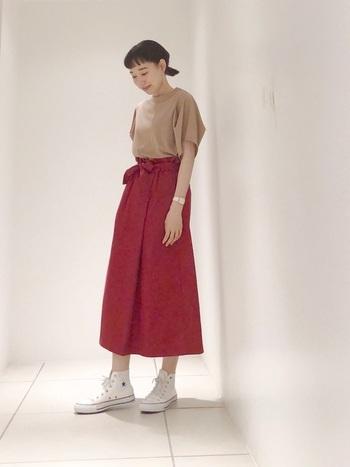 コーディネートの主役になるレッドのフレアスカート。その色の美しさが引き立つよう、トップスにはベージュの無地Tシャツを指名!