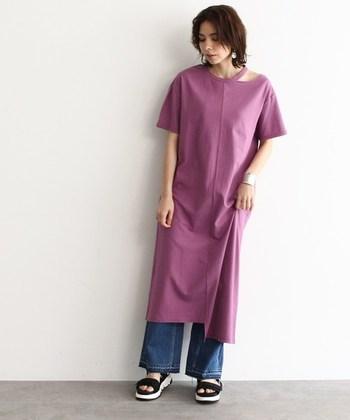 濃いピンクカラーのTシャツワンピースに、デニムワイドパンツとサンダルを合わせてカジュアルに。首元がさりげなくアシンメトリーなデザインになっているので、着るだけでサマになります。