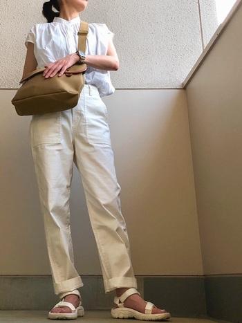 ギャザーブラウスにきちんと感のある白パンツをロールアップして合わせています。足元にはスポーツサンダルを合わせて、ちょっぴりカジュアルに。今年らしい白コーデです。