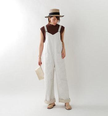 白のサロペットパンツに、ブラウンのトップスを合わせた着こなしです。サンダルとクラッチバッグとハットをベージュで揃えて、ナチュラルなカラ―リングでまとめたコーディネートです。