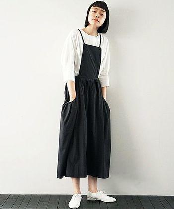 ワイドなシルエットの黒サロペットパンツは、白トップスを合わせてベーシックな着こなしに。足元には真っ白なスニーカーをプラスして、大人のリラックススタイルの完成です。