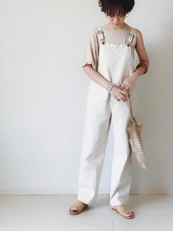 白のサロペットパンツに、ベージュのアシンメトリーデザイントップスを合わせたコーディネートです。サンダルとバッグも色を合わせて、トップスを主役に据えたナチュラルなのにハイセンスな着こなしに。