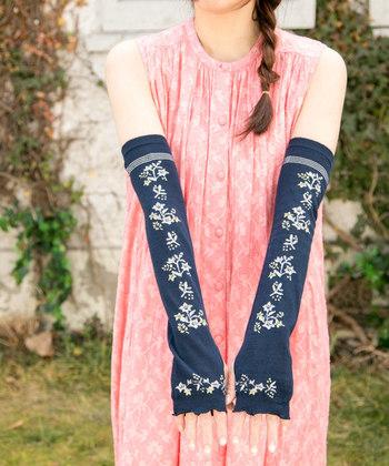 ネイビーカラーに花柄が描かれた、女性らしいデザインのアームカバーです。約45センチの長さで、手の甲から二の腕までをしっかりカバーしてくれます。