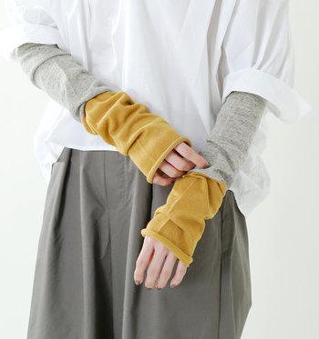 面麻素材で作られたアームカバーは、マスタードカラーとグレーをレイヤードしているように見えるデザインが魅力的なアイテムです。