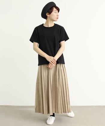 黒の半袖トップスに、ベージュのプリーツスカートを合わせた着こなしです。ナチュラルカラーのベージュと白シューズを合わせることで、黒アイテムを爽やかに見せているのがポイント。