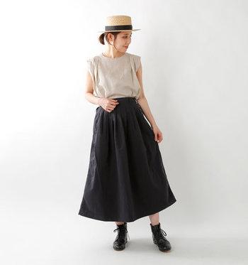 黒のAラインスカートに、ベージュのノースリーブトップスを合わせた着こなしです。シューズも黒で合わせ、肌の色ちらりと覗かせてコントラストを作ることで重さを軽減しています。ナチュラルカラーのハットとベージュトップスの組み合わせが、柔らかな印象に。