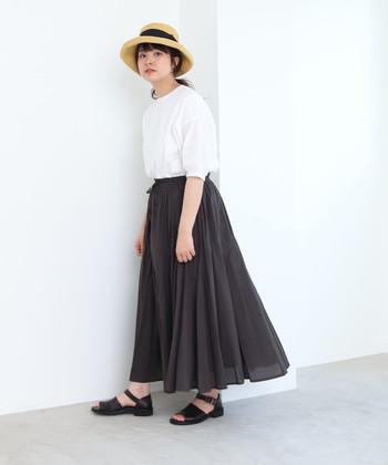 白の半袖トップスを、黒のロングスカートにタックインしたコーディネートです。足元も黒のサンダルでモノトーンに仕上げつつ、ゆとりのあるハットで、ナチュラルで涼しげな季節感をプラスしています。