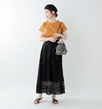 黒のロングスカートに、オレンジのTシャツをタックインした着こなしです。ロングスカートの裾がレースで透け仕様になっているので、さりげなく覗く脚のラインが涼しげな印象を与えてくれます。