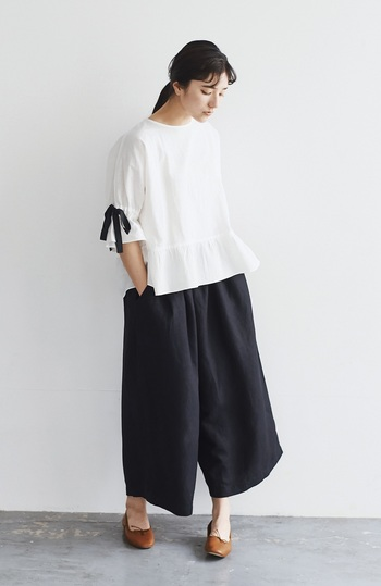 黒のキュロットスカートに、白のブラウスを合わせた上品とラフさを兼ね備えたコーディネートです。足元はブラウンのパンプスを合わせて、落ち着きを持たせつつ、きちんと感のあるコーディネートに。