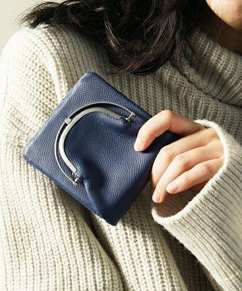 周りのフレームを歪ませることで、開閉ができるというちょっぴり変わったデザインのがま口財布です。シックなネイビーカラーで、男女を問わずに使えるのも魅力的。