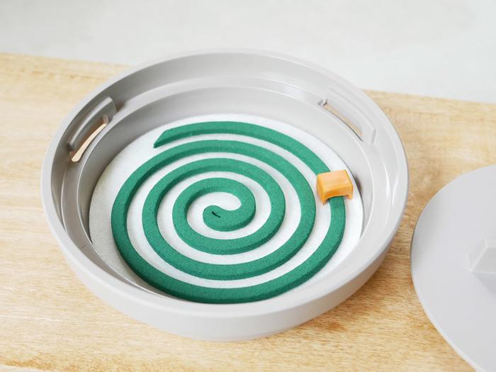 中には不織ガラスファイバーシートが敷かれていて、蚊取り線香をそのままセットすることができます。オレンジ色のものは火消しタイマー。燃えている蚊取り線香に触れることなく、安全に火を消すことができます。