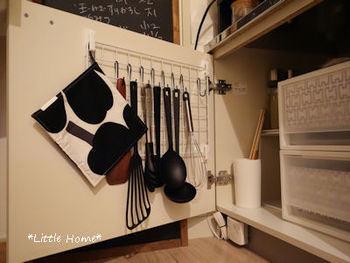 かさばるキッチンツールもキッチン扉裏に。ひとつずつフックにハンギングすれば、より取り出しやすくなりますね。
