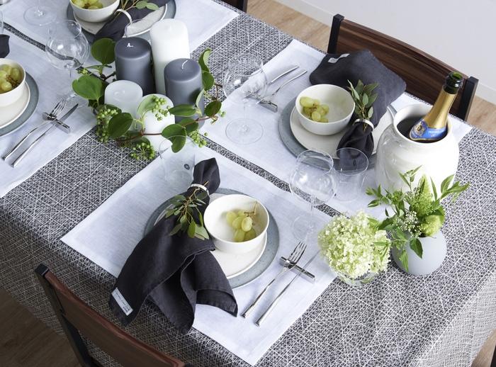 爽やかな風が通り抜けるような大人っぽい初夏のテーブルコーディネート。センターピースには、ホワイトとグレーのシックなキャンドルを並べ、グリーンのサンキライを添えてさり気なく季節感を演出しています。