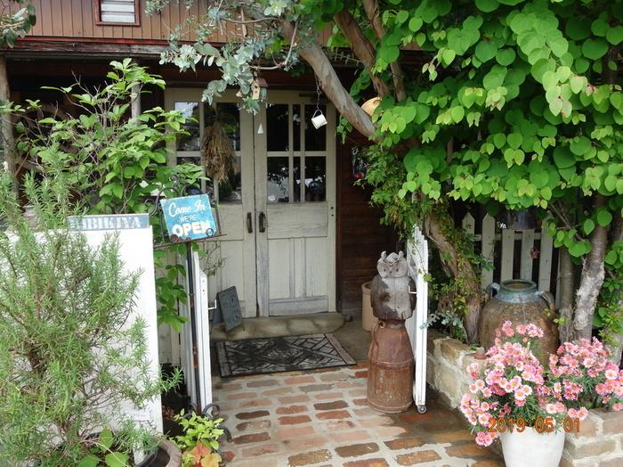 邑楽郡大泉町の住宅街にたたずむ「カフェひびきや」は、たくさんの草花に囲まれた外観が印象的。白いドアの前に立つと、なんだか森の中にいるような気分になりますね。