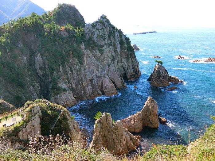 鳥取砂丘から、日本海側にそって兵庫県方面へ、20分ほどドライブを。目的の地は、鳥取市の隣町、岩美町の浦富海岸です。  浦富海岸は、山陰海岸ジオパークに指定されている、東西15kmのリアス式海岸。荒波などによって削られた岩など、ここならではの絶景に出会えます。