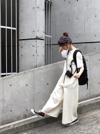 ワイドサロペット&Tシャツの爽やかなオールホワイトコーデに、大きめの黒リュックのラフなバランスが今年らしい。靴や小物も黒にすることで、全体が引き締まります。