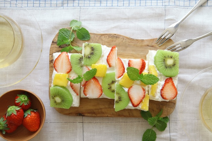 食パンの耳をとり、パンに生クリームを塗ったら薄くスライスしたフルーツをバランスよく乗せていきます。キウイ・パイン・いちごなど、色とりどりのフルーツを添えれば見た目も鮮やかです。