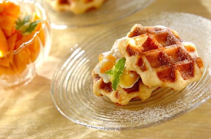 ワッフルに酸味の効いたマンゴーヨーグルトクリームを挟んだデザートのワッフルサンド。冷やしたクリームをあたたかいワッフルに挟むとおいしそう♪