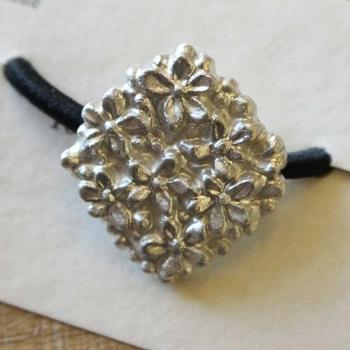 陶磁器でつくられたヘアゴムは、「星の花」という名前がつけられています。華やかになりすぎず、シックに仕上げたい大人のまとめ髪にぴったりのヘアアクセサリーです。