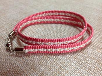 京組紐の伝統工芸士によるオリジナルデザイン。縦糸と横糸の構成で織物に近い雰囲気も出せる綾竹組で作られており、中央の小桜が可憐です。
