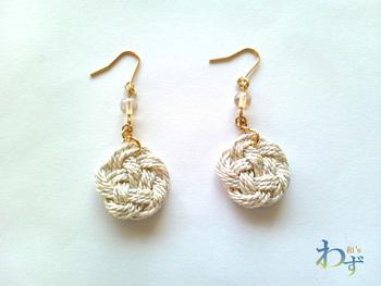 落ち着きのある梅結びのピアス。生成りと金糸が混ざった上品な雰囲気で、どんな季節、どんなシーンにもなじみます。