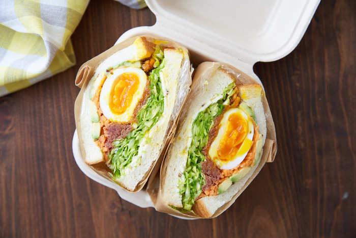 たっぷりの具材でボリューム満点のサンドイッチです。ゆで卵まるごと1個にたくさんの野菜とコンビーフが入っています。サンドする時はラップで包んでなじませるのがポイント。切る前にワックスペーパーで包めば崩れにくくなります。