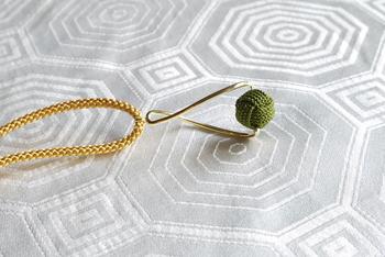 美しいラインのチャームと組紐が素敵なハーモニーを織りなすネックレス。モダンで個性的な味わいを引き立てるために、シンプルな洋服と合わせるといいかも。