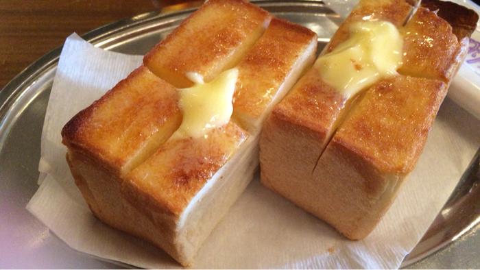 """浅草で知らない人はいないであろう老舗ベーカリー「ペリカン」のパンを使った厚切りトースト。焼き加減も絶妙で、外はサクサク、中はもっちりとしていてパンの風味が口いっぱいに広がります。まさに""""魔性の味""""、感動必至のおいしさです。"""