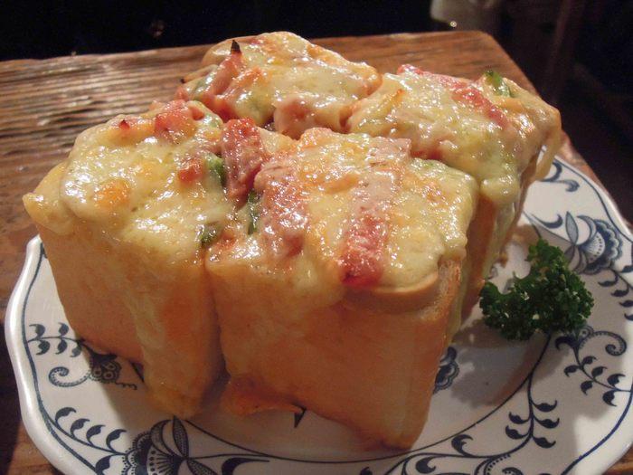 ピーマンやハムなどの具材とチーズを乗せた、人気のピザトースト。4枚切りよりさらに分厚くカットされたパンは、ふかふかしていて、表面を覆いつくすたっぷりのチーズと相性抜群。満足感のある一品です。
