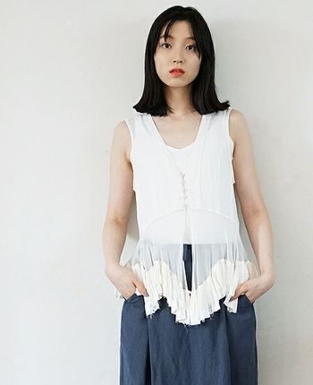 """""""時間と調和""""をコンセプトに繊細で緊張感のある服を展開する「suzuki takayuki」。こちらは、裾にシルクのフリルをあしらった透明感のあるジレです。"""