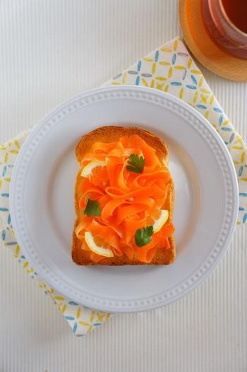 ピーラーを使ってにんじんを細く切り、レモンやオリーブオイルと一緒に冷蔵庫で冷やします。バターを塗ったトーストの上にトッピングすれば、見た目にも鮮やかなヘルシートーストに!