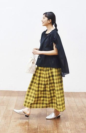パッと目を引くイエローのチェック柄スカートに、黒のふんわりトップスを合わせたコーディネート。あえてタックインせずにゆるっと着こなすことで、夏の涼しげな雰囲気をアピールできます。