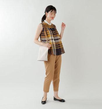 チェック柄のノースリーブシャツに、同系色の七分丈パンツを合わせたコーディネートです。ワイドとタイトなシルエットの組み合わせで、チェック柄をスッキリと着こなしています。