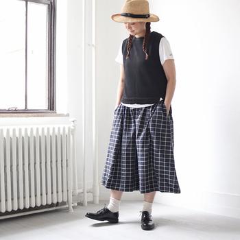 ネイビーのチェック柄スカートに、白Tシャツと黒のベストを合わせたコーディネートです。きちんと感のあるマニッシュ風スタイルに、ハットでナチュラルなアクセントをプラスしています。