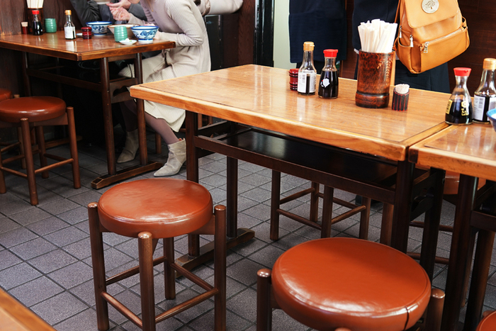 行列の絶えない人気店ですが、小さなテーブルと丸いすが置かれたとてもこじんまりした店内です。混雑時は相席が必至です。
