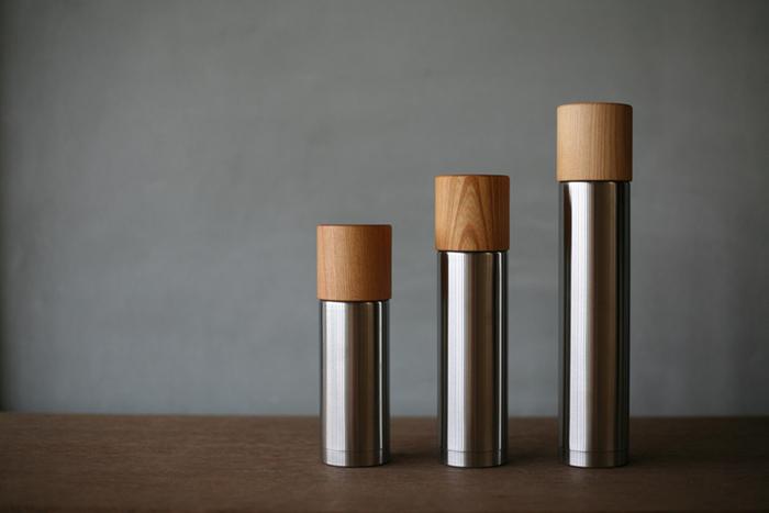"""""""SUSgallery""""のステンレスボトルと木地師がろくろで挽いたコップが一つになった「MokuNeji Bottle」。木目とステンレスのコントラストがとても美しい水筒は、品のある佇まいがとっても魅力的!""""SUSgallery""""が誇る高い保温・保冷性能はそのままに、手ざわりも口当たりも優しい木製コップを組み合わせることで、他にはない特別感を感じることができます。 欅(けやき)のコップは、美しい木目は勿論、熱伝導率が低いので、熱いコーヒーやお茶など、熱い飲み物を注いでも手に熱さが伝わりにくくなっています。"""