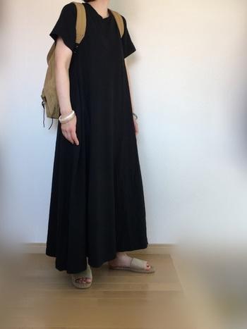 ボリュームのあるマキシ丈の黒ワンピースに、ベージュのリュックでまろやかさをプラス。足元もリュックと同色のフラットサンダルで、リラクシーなスタイリングです。