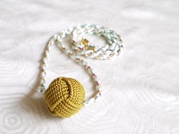 「あわじ玉」は、先述の「あわじ結び」を複数回(写真のあわじ玉は2回)繰り返して、引き締めながら丸く形作ります。コロンとした形は、ネックレスやピアス、リング、ボタンなど、さまざまなアイテムにアレンジしやすそうですね。