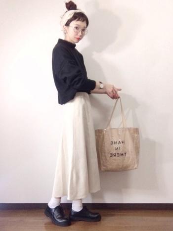 アイボリーのスカートに、同系色のターバンを合わせて。重めの印象の黒のトップスをアイボリーの上下で挟むことにより、優しげな印象に。