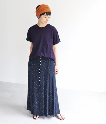 シンプルなクルーネックには、柄物のスカートとターバンを合わせておしゃれに。服は紺色でまとめて、オレンジのターバンがアクセントになって夏らしいさわやかなコーデです。