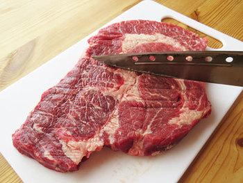 あれば肉叩き、無ければ包丁の背でステーキ肉の両面をまんべんなくほどほどに叩きます。また、包丁の刃先を使い、透明な筋を数か所刺すように筋切りしておきます。