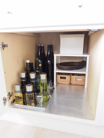 シンク下の奥には瓶入りの調味料、手前には背の低い調味料を収納。 背の高いモノを奥から順に置いていくと、どこに何があるか一目でわかります。
