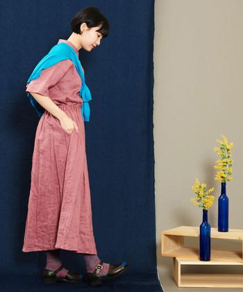 ピンクのシャツワンピースに、ブルーのカーディガンを肩から羽織ったコーディネートです。反対色の組み合わせが良いアクセントになりますし、袖を通せば寒さやUVや対策にも活用できます。