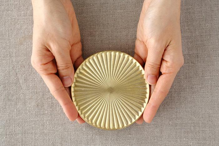 真鍮製の生活用品でお馴染みの「フタガミ/FUTAGAMI」のコースター。一筋に伸びる光を意味する「光芒」と言う名のコースターは、美しい佇まいがとても魅力的で、中心から外側に向けて広がるいくつもの光の筋があることで、水滴が分散され、コースターがコップにくっつくのを防いでくれます。真鍮ときくと、テーブルを傷つけてしまう…?と一見思いますが、裏面にはシリコンが高台をぐるりと巡っているので滑りにくく、お気に入りのテーブルを傷つけてしまうといった心配もありません。