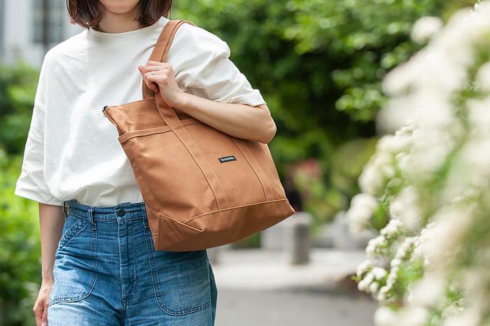 長めの持ち手が付いているので、肩にかけたまま荷物を出し入れすることも可能。内側には、細々したものを収納するのにピッタリの2つのポケットと、貴重品入れに便利なファスナー付きのポケットもしっかり内臓されています。