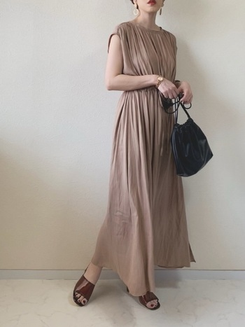 ギャザーが贅沢にあしらわれたロング丈のワンピースは、大人の女性らしさを演出。同系色のサンダルと合わせて軽やかな夏の装いに。