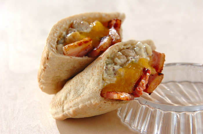 キュウリのピクルス、水煮のヒヨコ豆、 カッテージチーズ、ブロックのベーコン、粒マスタード、マヨネーズで作るヒヨコ豆のサラダをピタパンで挟んだビーンズサンド。ヘルシーでボリュームも味も大満足のサンドイッチは、ピクニックランチや、持ち寄りパーティーにも使えそう。